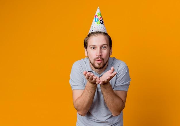 생일 파티를 축하하는 휴일 모자를 가진 젊은 남자가 행복하고 긍정적 인 오렌지 벽 위에 서있는 그 앞에서 손으로 키스를 불고