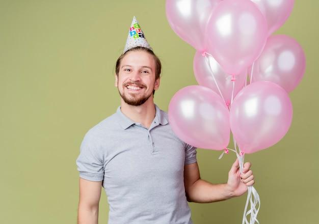 풍선을 들고 생일 파티를 축하하는 휴가 모자와 젊은 남자 미친 행복하고 빛 벽 위에 유쾌하게 서 웃는 흥분