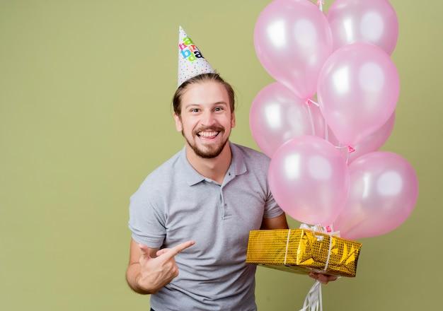 Giovane con tappo di festa che celebra la festa di compleanno che tiene il regalo di compleanno e palloncini sorridendo felice ed eccitato allegramente in piedi sopra la parete chiara