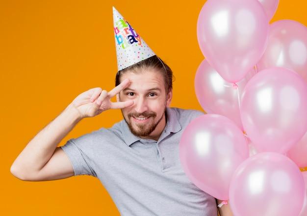 Giovane con tappo di vacanza che celebra la festa di compleanno tenendo un mazzo di palloncini sorridendo allegramente mostrando segno v in piedi sopra la parete arancione