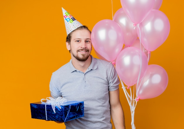 オレンジ色の上に幸せで陽気な風船と誕生日プレゼントの束を保持している誕生日パーティーを祝うホリデーキャップを持つ若い男