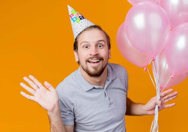 생일 파티를 축하하는 휴일 모자를 가진 젊은 남자가 행복하고 흥분된 풍선의 무리를 들고 오렌지 위에 넓게 웃고