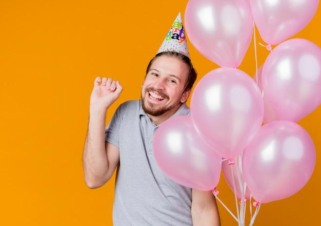 생일 파티를 축하하는 휴일 모자를 가진 젊은이 행복하고 흥분된 풍선을 들고 오렌지 벽 위에 유쾌하게 서서 웃고