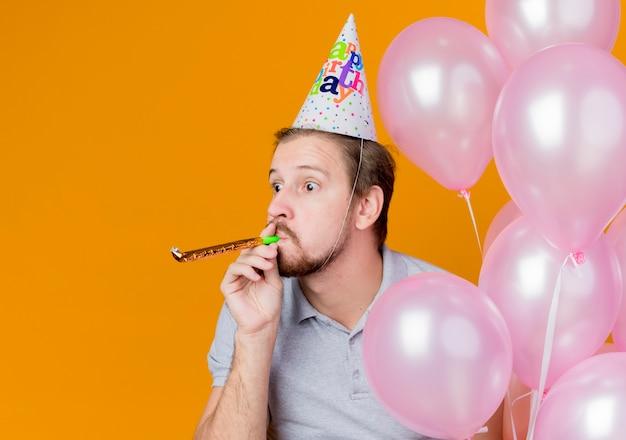 オレンジ色の上に幸せでポジティブな風船の束を保持している誕生日パーティーを祝うホリデーキャップを持つ若い男