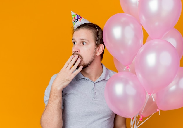 オレンジ色に驚いて驚いた手で口を覆って脇を見ている風船の束を保持している誕生日パーティーを祝うホリデーキャップを持つ若い男