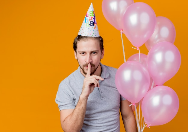オレンジ色の壁の上に立っている唇に指で沈黙のガスを作る風船の束を保持している誕生日パーティーを祝うホリデーキャップを持つ若い男