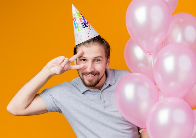 생일 파티를 축하하는 휴일 모자를 가진 젊은 남자가 오렌지 벽 위에 서있는 v 기호를 유쾌하게 보여주는 풍선의 무리를 들고 웃고