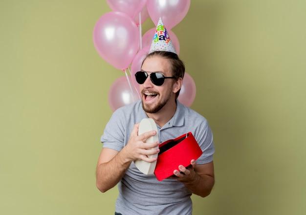 휴일 모자 선물 상자를 들고 생일 파티를 축하하는 젊은 남자가 행복하고 빛 벽에 풍선과 함께 유쾌하게 서 웃고 흥분