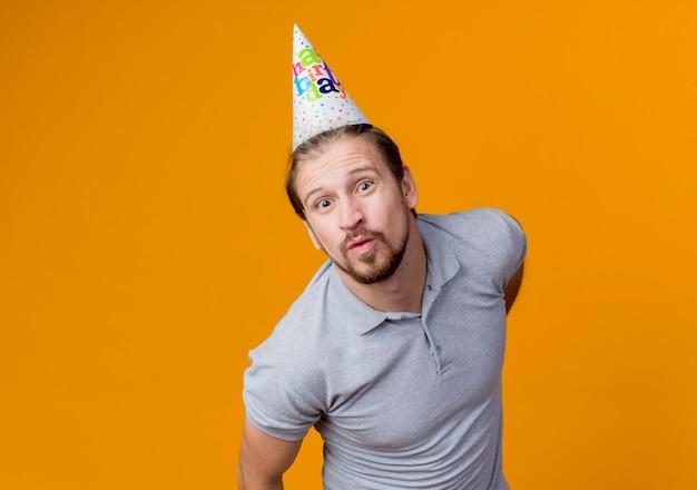 오렌지 벽 위에 행복하고 쾌활한 서 키스를 입술을 유지하는 생일 파티를 축하하는 휴일 모자와 젊은 남자