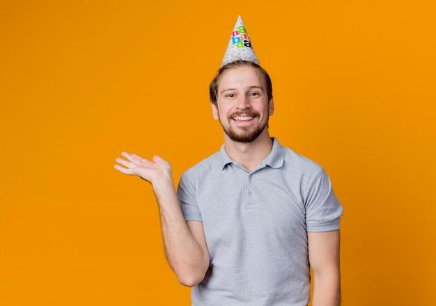생일 파티를 축하하는 휴일 모자를 가진 젊은 남자가 행복하고 쾌활한 오렌지 벽 위에 광범위하게 서있는 미소로 뭔가를 제시합니다.
