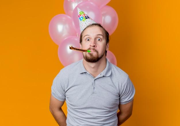 풍선과 함께 생일 파티를 축하하는 휴가 모자와 젊은 남자가 오렌지 벽 위에 서 놀란