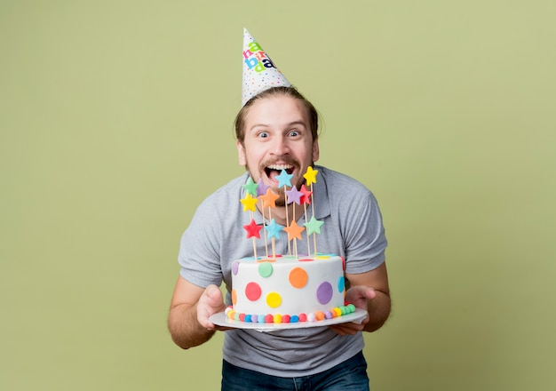 光に幸せで興奮して誕生日パーティーを祝うバースデーケーキを保持しているホリデーキャップを持つ若い男