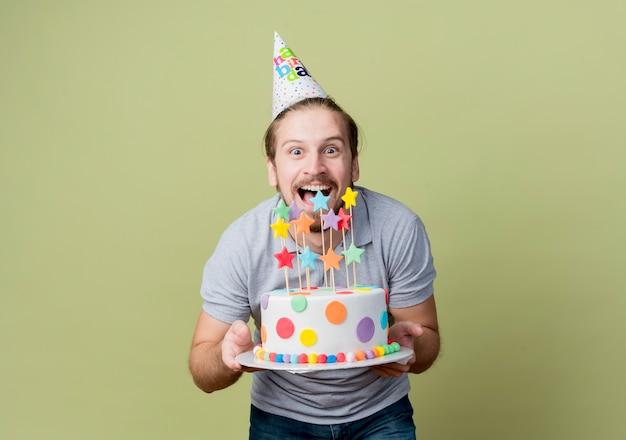 Giovane con tappo di festa che tiene la torta di compleanno che celebra la festa di compleanno felice ed eccitato sopra la luce