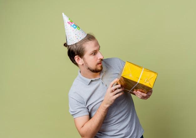 Молодой человек в праздничной кепке с подарком на день рождения, глядя на него, удивился концепции вечеринки по случаю дня рождения, стоя над светлой стеной