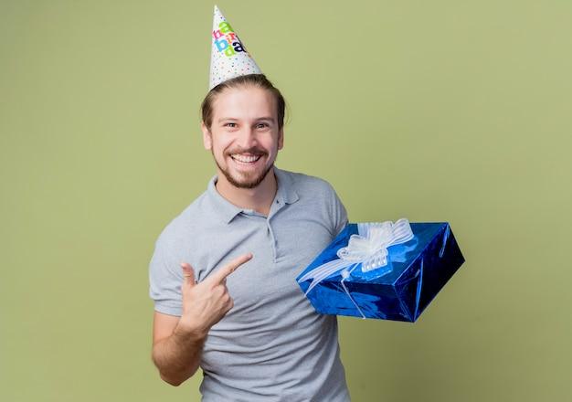 Молодой человек с праздничной кепкой держит подарок на день рождения, улыбаясь, празднует день рождения, счастлив и взволнован над светлой стеной