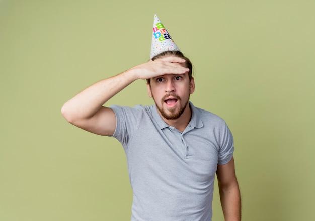 Giovane uomo con cappello vacanza guardando lontano con la mano sopra la testa sorpreso in piedi sopra la parete leggera