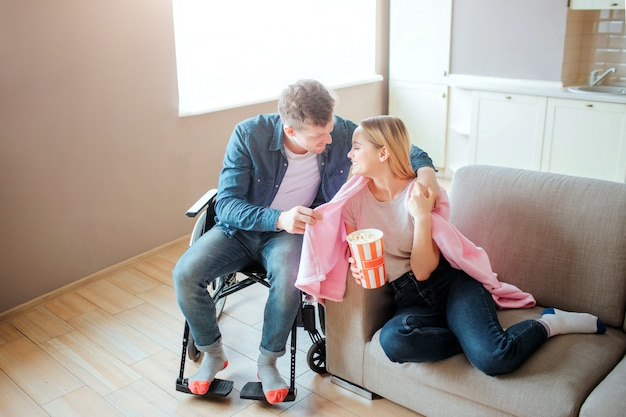 Young man with inclusiveness take care of girlfriend. he covers her shoulder with blanket and smile. person with special needs. sitting on wheelchair.