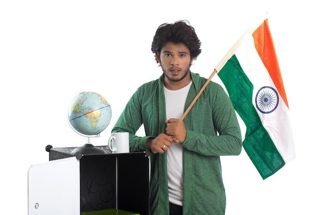 Молодой человек с индийским флагом или триколором с глобусом на белом