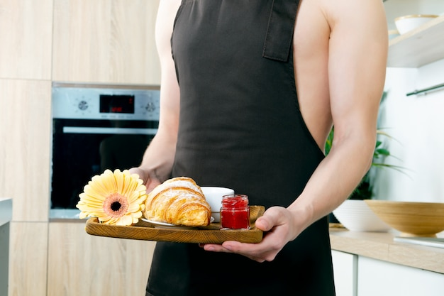 Young man with inflated naked torso in brown apron