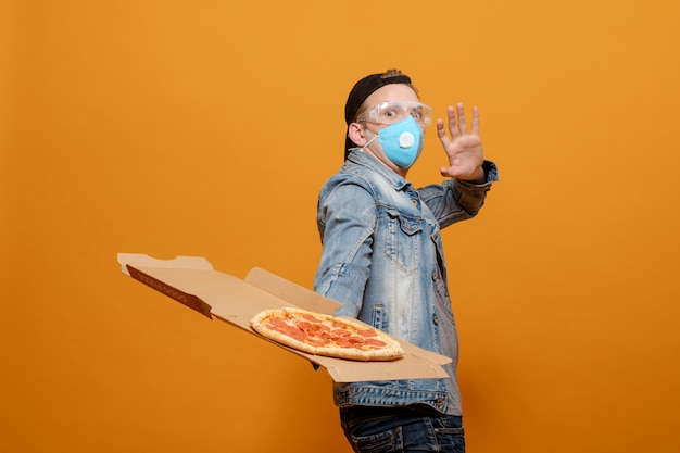 Young man with italian pizza pepperoni, pizza delivery,  pandemic and quarantine