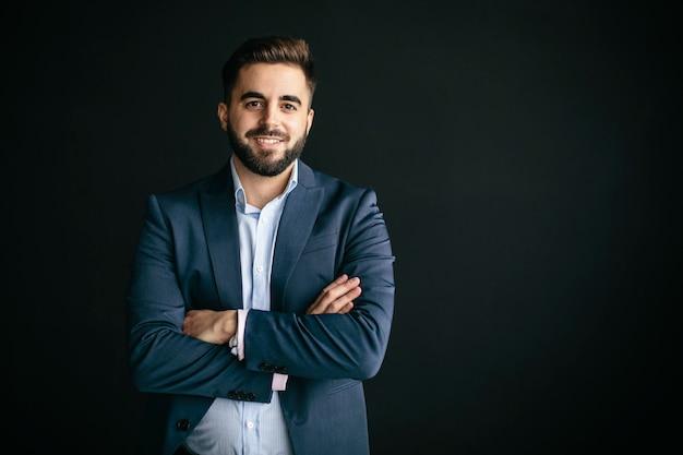 Молодой человек в куртке и рубашке, похожий на предпринимателя, улыбается, скрестив руки. в стене уличного фона. концепция работы и молодых предпринимателей
