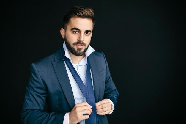 Молодой человек в пиджаке и рубашке, похожий на предпринимателя, в галстуке, смотрит в камеру. в черной стене уличного фона. концепция работы и молодых предпринимателей
