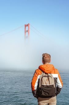 A young man with a jacket stands on the embankment and looks at the fog covering the golden gate