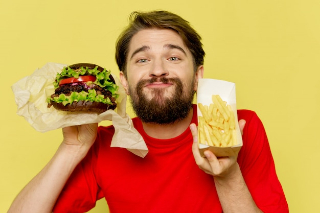 Young man with a juicy hamburger and fires in his hands