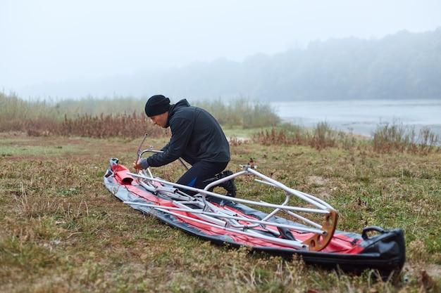 Молодой человек с каяком на берегу красивой реки или озера ранним утром