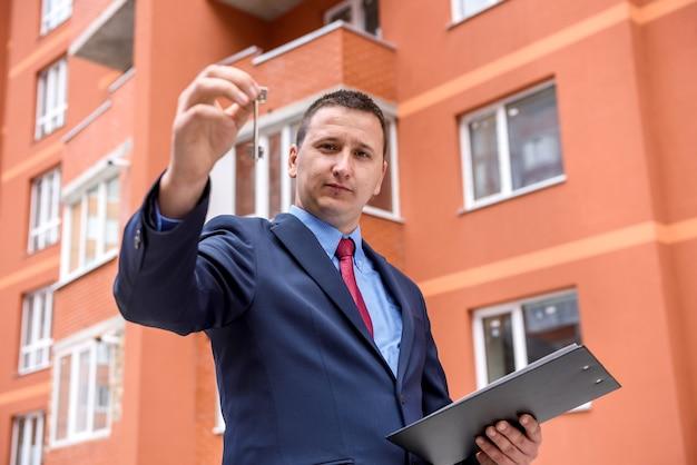 Молодой человек с ключом стоит перед новым зданием