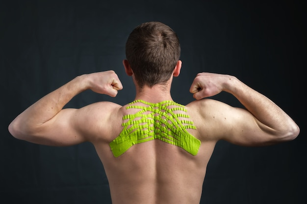 Young man with kinesiology medical tape on his neck showing biceps