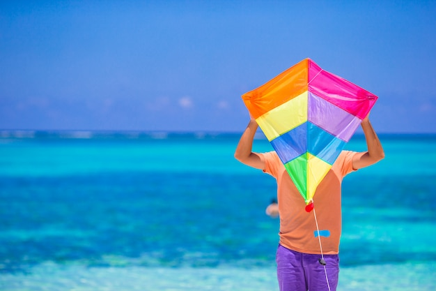 Young man with a kite on a background of turquoise sea