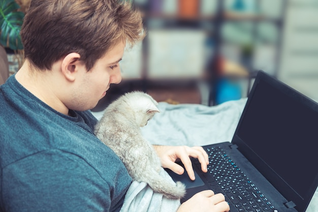 彼のラップトップで働いている子猫と若い男。オンライン学習と仕事の概念。