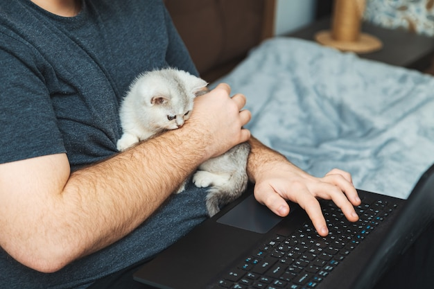 그의 노트북에서 일하는 고양이와 젊은 남자. 온라인 학습 및 작업의 개념.