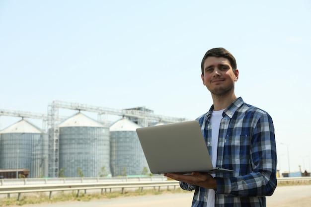 穀物サイロに対してラップトップを持つ若者。農業事業