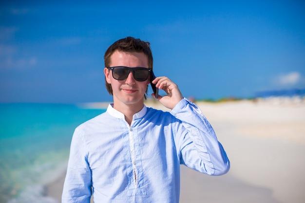ラップトップと熱帯のビーチでターコイズブルーの海の背景に電話と若い男