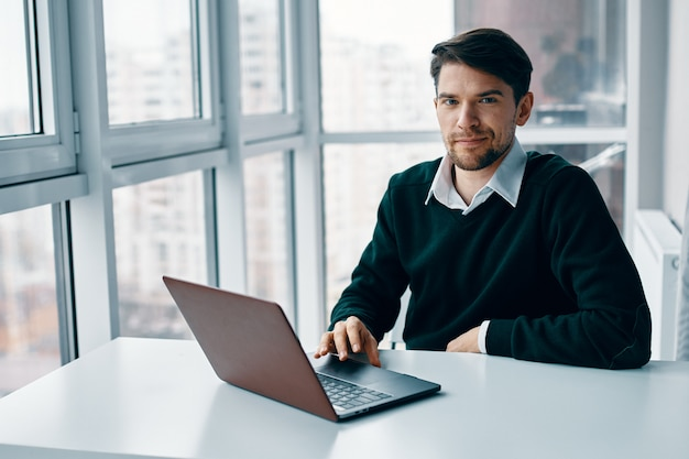 Young man with a laptop in a business suit working in the office and at home, interviewing online