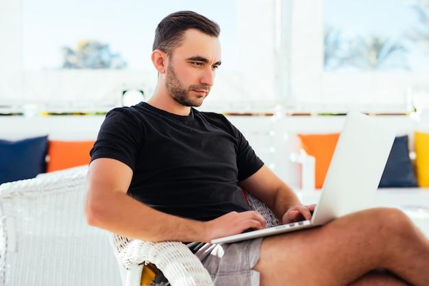 夏休みの屋外カフェでラップトップコンピューターを持つ若い男