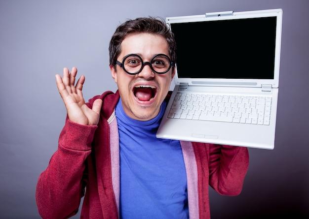 Молодой человек с портативным компьютером на сером