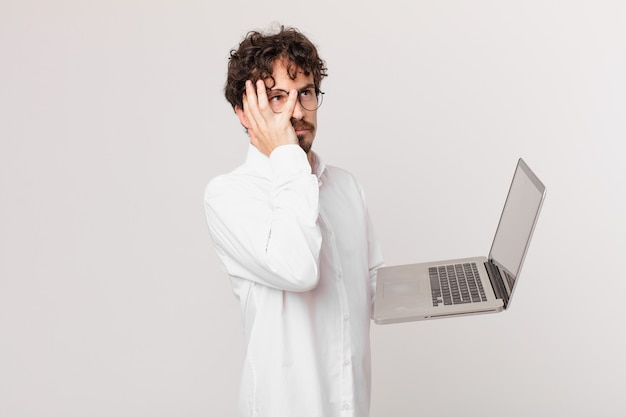 Young man with a laptop feeling bored, frustrated and sleepy after a tiresome