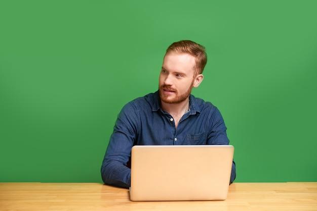 緑の背景で隔離のラップトップを持つ若い男