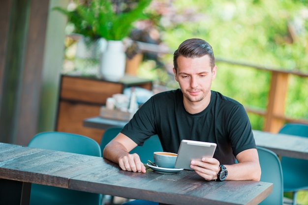 Young man with laptop in outdoor cafe drinking coffee. man using mobile smartphone.