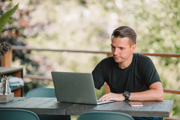 Young man with laptop in outdoor cafe drinking coffee.