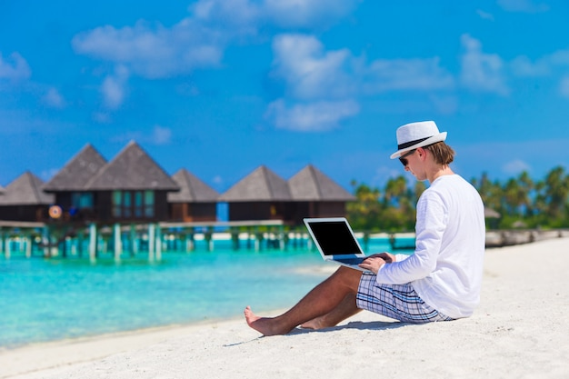 Young man with laptop at tropical beach near water villa