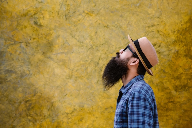 Young man with a long beard wearing a hat and glasses