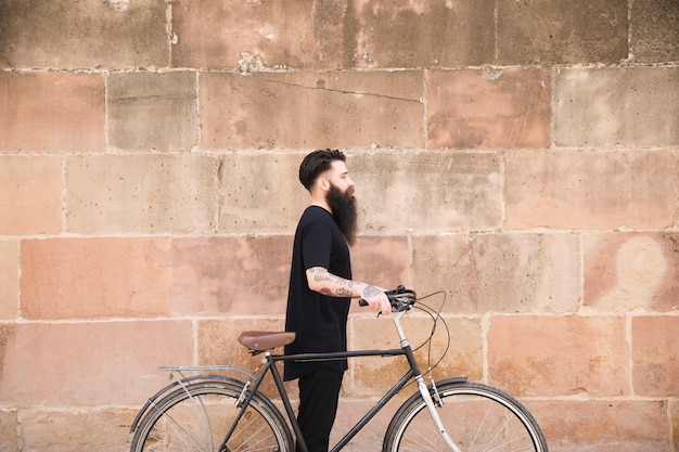 Young man with long bearded man standing with bicycle against wall