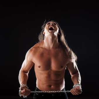 Young man with long hair breaks the iron chain.