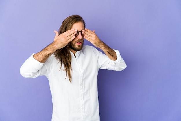 Young man with long hair look afraid covering eyes with hands.