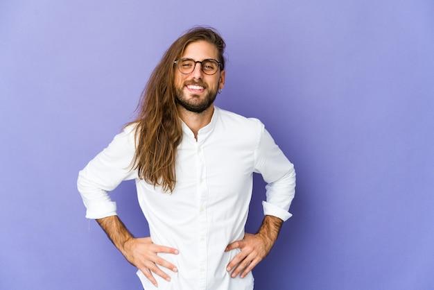 Молодой человек с длинными волосами выглядит уверенно, держа руки на бедрах