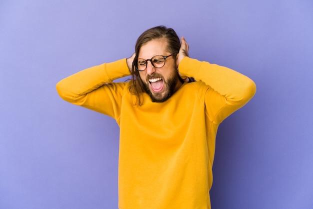 Молодой человек с длинными волосами смотрит, закрывая уши руками